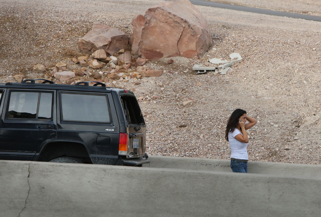 A woman talks on her cell phone at the accident scene where a crash has blocked all northbound lanes of U.S. Highway 95 at the Spaghetti Bowl Friday, Dec. 5, 2014. Nevada Highway Patrol responded  ...