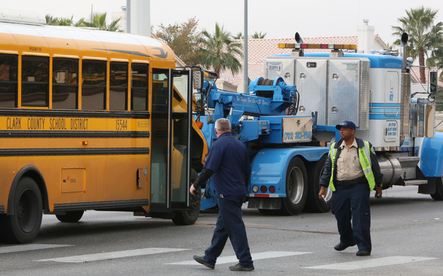 A school bus is ready to be towed from the accident scene Friday, Dec. 5, 2014, where one person was injured after a crash involving a sedan in the Cheyenne Avenue and Soft Breezes Drive intersect ...