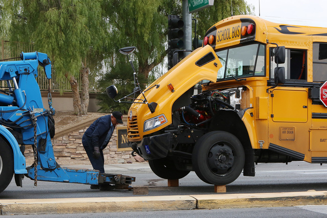 A worker prerpares to tow a school bus from the accident scene Friday, Dec. 5, 2014, where one person was injured after a crash involving a sedan in the Cheyenne Avenue and Soft Breezes Drive inte ...
