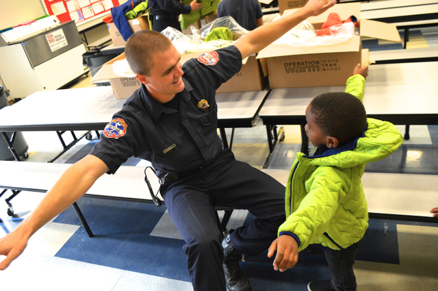 Professional Fire Fighters of Nevada David Carraway interacts with a student at Quannah Mccall Elementary School, Tuesday, Dec. 16, 2014. Firefighters visited the school to deliver coats to childr ...