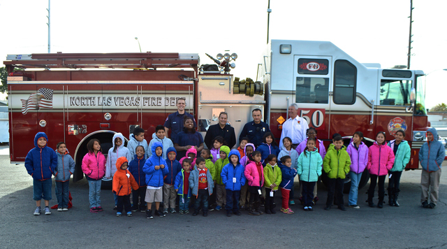 """Students at Quannah Mccall Elementary School pose for a photo, Tuesday, Dec. 16, 2014. Firefighters visited the school to deliver coats to children in need through the """"Coats for Kids"""" campaig ..."""