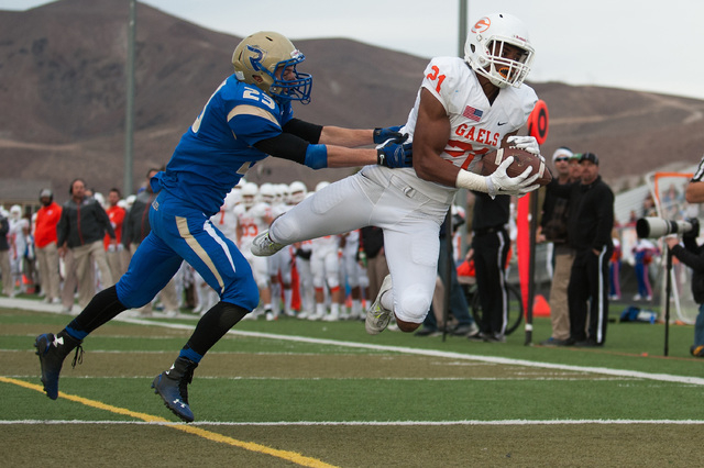 Bishop Gorman's Cordell Broadus (21) catches a touchdown pass against Reed's Porter Hansen (23) during the second half of the NIAA Nevada State High School Division I Championship game at Damonte  ...