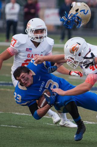 Reed's Porter Hansen (23) gets hit hard by Bishop Gorman's Gage Wilson (42) during the second half of the NIAA Nevada State High School Division I Championship game at Damonte Ranch High School on ...