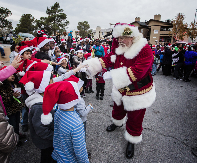 Santa Claus greets children during a community block party Friday, Dec. 19, 2014 at the Sierra Oeste community in northwest Las Vegas. One year ago police and other community groups launched an in ...