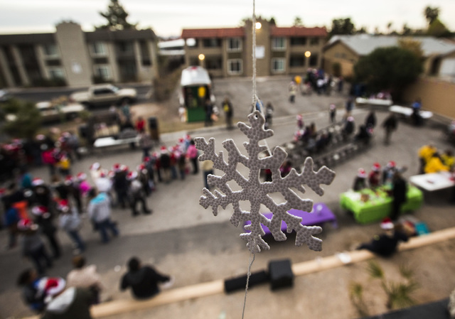 A Christmas ornament hangs from a second floor apartment during a community block party Friday, Dec. 19, 2014 at the Sierra Oeste community in northwest Las Vegas. One year ago police and other co ...