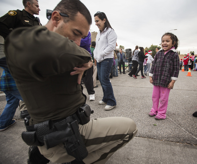Metro Officer Jay Martinez,left, looks for a badge to give to Bella Vadquez, 4,  Friday, Dec. 19, 2014 during a community block party at the Sierra Oeste community in northwest Las Vegas. One year ...
