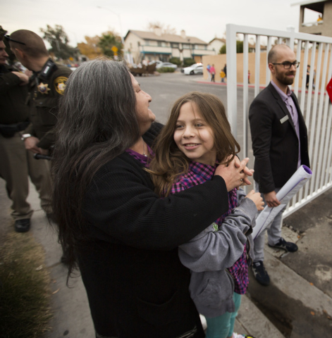 Joann Barraza,left hugs her granddaughter Brianna Clawson, 10, Friday, Dec. 19, 2014 during a community block party at the Sierra Oeste community in northwest Las Vegas. One year ago police and ot ...