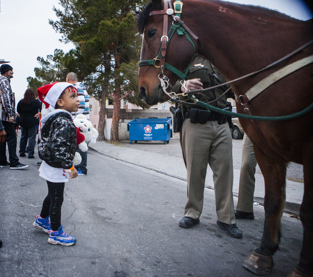 Adrianna Wilson, 3, looks at the horse from the Metropolitan Mounted Police Unit Friday, Dec. 19, 2014 during a community block party at the Sierra Oeste community in northwest Las Vegas. One year ...