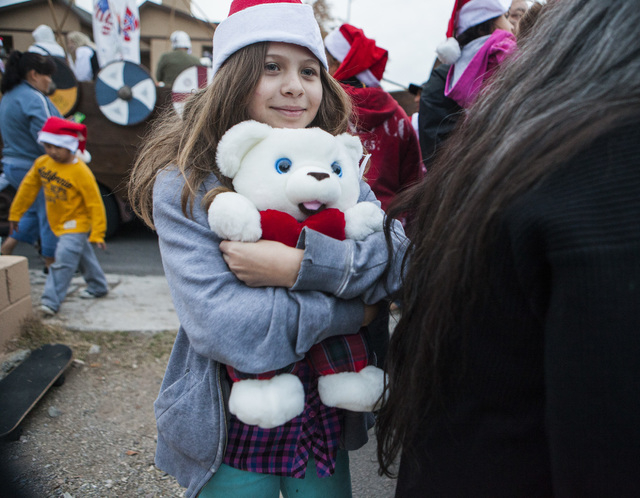 Brianna Clawson, 10, holds Snuggles a teddybear that she got  Friday, Dec. 19, 2014 during a community block party at the Sierra Oeste community in northwest Las Vegas. One year ago police and oth ...