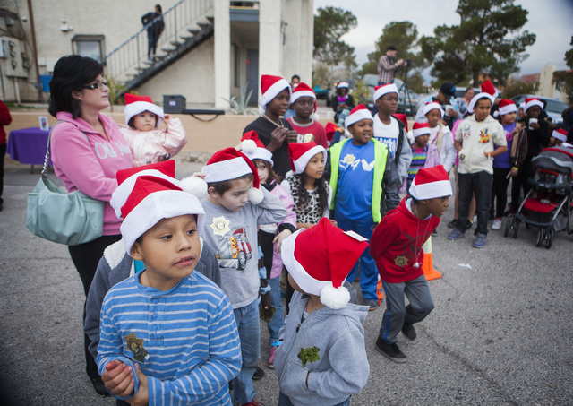 Children stand in line to meet Santa Claus  Friday, Dec. 19, 2014 during a community block party at the Sierra Oeste community in northwest Las Vegas. One year ago police and other community group ...