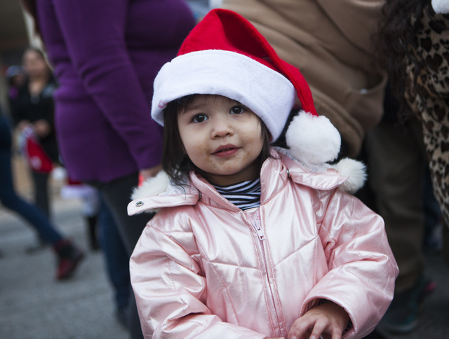 Jaycee Cervantes, 2, waits in line to meet Santa Claus Friday, Dec. 19, 2014 during a community block party at the Sierra Oeste community in northwest Las Vegas. One year ago police and other comm ...