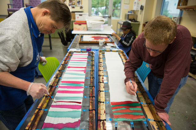 Opportunity Village clients Scott R., left, and Cory B. (last names withheld) paint scarves to sell at Opportunity Village's Ralph and Betty Engelstad Campus, 6050 S. Buffalo Drive, Dec. 4, 2014.  ...