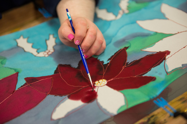 Inesa M. (last name withheld), a client at Opportunity Village, paints a scarf to sell at Opportunity Village's Engelstad Campus Dec. 4, 2014. (Samantha Clemens-Kerbs/View)
