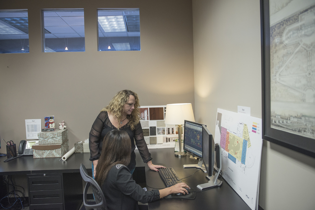 Kellie Wanbaugh, Project Manager, top and Carina Gaytan, Interior Design Assistant, look over a design at Ed Vance and Associates in Las Vegas on Friday, December 19, 2014. Ed Vance and Associates ...