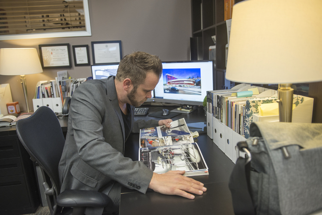 Kevin Welch, Design Director at Ed Vance and Associates, looks over a book of work at his office in Las Vegas on Friday, December 19, 2014. Ed Vance and Associates offers holiday bonuses, holiday  ...