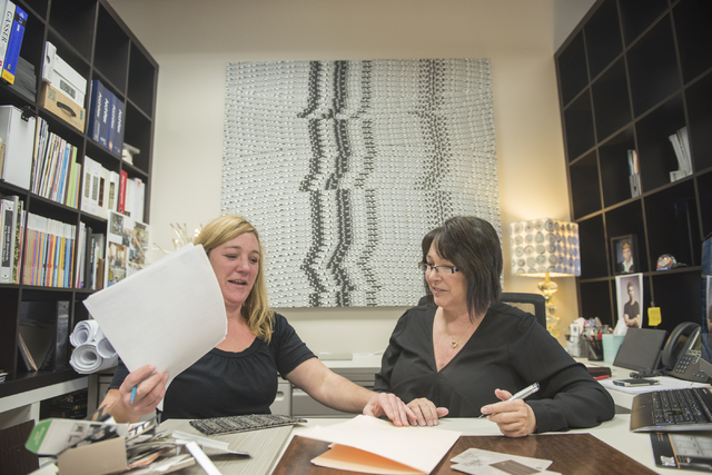 Ed Vance and Associates employees, Jennifer Blanchard, controller, left, and Jonelle Vance, executive vice president, discuss work in Las Vegas on Friday, December 19, 2014. Ed Vance and Associate ...