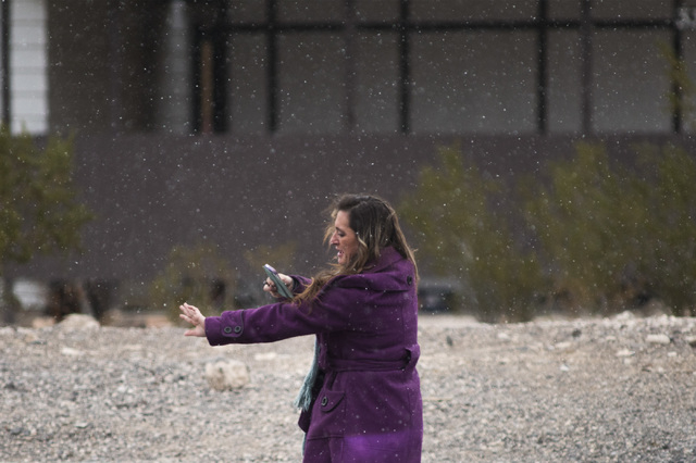 A woman stops on a roadside to take a selfie in a brief snow shower in Henderson on Wednesday, Dec. 31, 2014. (Mark Damon/Las Vegas Review-Journal)