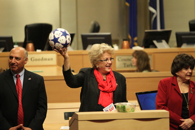 Las Vegas Mayor Carolyn Goodman, center, holds up a ball she received as a gift, with Mayor Pro Tem Stavros Anthony, left, and Councilwoman Lois Tarkanian, during a Las Vegas City Council meeting  ...