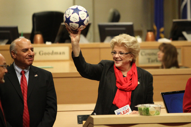 Las Vegas Mayor Carolyn Goodman, center, holds up a ball she received as a gift, with Mayor Pro Tem Stavros Anthony, left, during a Las Vegas City Council meeting before a vote for a proposed socc ...