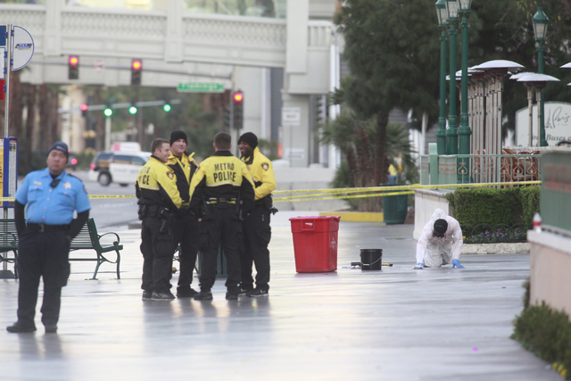 An employee of Logistical Solutions, right, cleans up the scene as Las Vegas police investigate a shooting involving a Regional Transportation Commission security officer and man, pronounced dead  ...