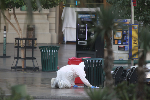 An employee of Logistical Solutions cleans up the scene as Las Vegas police investigate a shooting involving a Regional Transportation Commission security officer and man, pronounced dead at the s ...