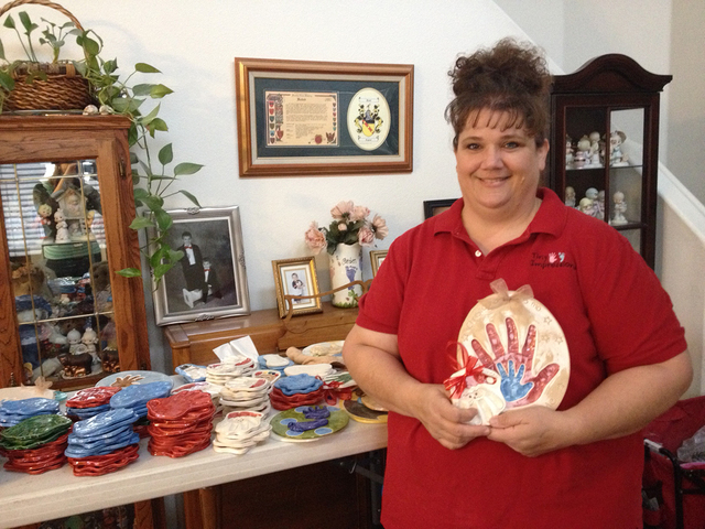 Connie Hallett poses with a few of her ceramic handprints and footprints at her home in Centennial Hills, Wednesday, Dec. 3, 2014. Hallett launched Tiny Impressions as an effort to stay at home wi ...