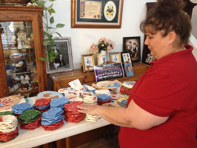 Connie Hallett describes a few of her holiday ceramic handprints and footprints at her home in Centennial Hills, Wednesday, Dec. 3, 2014. Hallett launched Tiny Impressions as an effort to stay at  ...