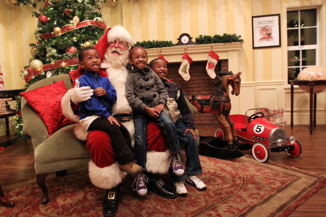 Santa sits for a photo with, from left, Keontrae Jordan, A'Narie Collins and Quaentan Collins in his house at Town Square Friday, Nov. 28, 2014. (Sam Morris/Las Vegas Review-Journal)