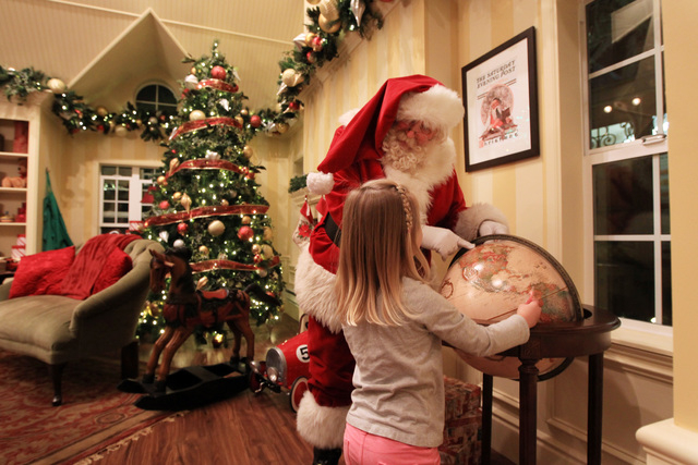 Santa shows a young girl where the North Pole is on a globe in his house at Town Square Friday, Nov. 28, 2014. (Sam Morris/Las Vegas Review-Journal)
