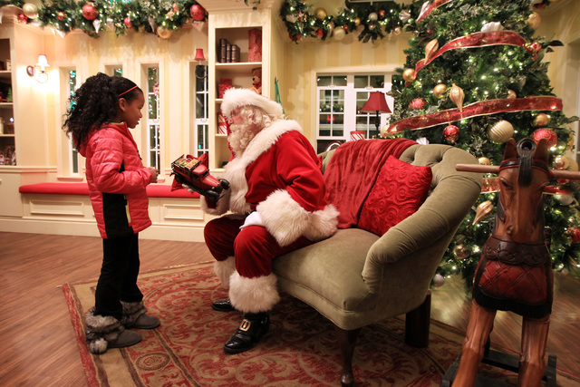 Santa shows Vianney Jordan a toy truck in his house at Town Square Friday, Nov. 28, 2014. (Sam Morris/Las Vegas Review-Journal)