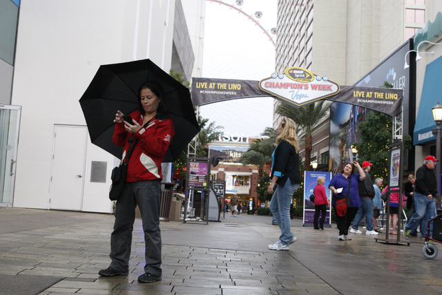 Hege Austvoll, a tourist from Norway, takes cover from the rain under her umbrella near The Linq in Las Vegas Tuesday, Dec. 2, 2014. (Erik Verduzco/Las Vegas Review-Journal)