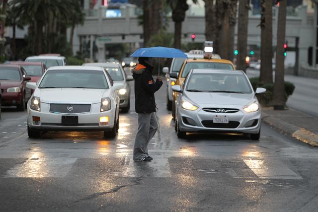 An unidentified walks across Las Vegas Boulevard with his umbrella near The Linq in Las Vegas Tuesday, Dec. 2, 2014. (Erik Verduzco/Las Vegas Review-Journal)