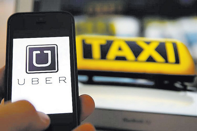 An illustration picture shows the logo of ride-sharing app Uber on a smartphone. (Kai Pfaffenbach/Reuters)