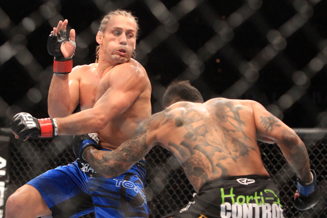 Urijah Faber takes a shot to the body from Francisco Rivera during their fight at UFC 181 Saturday, Dec. 6, 2014 at the Mandalay Bay Events Center. Faber won by submission. (Sam Morris/Las Vegas R ...