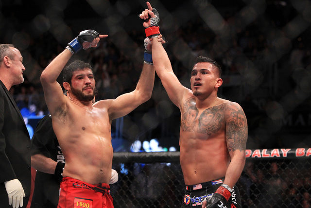 Anthony Pettis has his hand raised by Gilbert Melendez after making Melendez tap out during their fight at UFC 181 Saturday, Dec. 6, 2014 at the Mandalay Bay Events Center. (Sam Morris/Las Vegas R ...