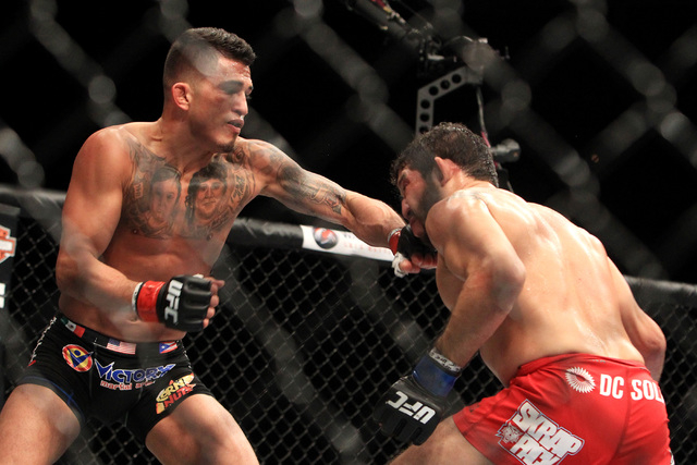 Anthony Pettis hits Gilbert Melendez with a left during their fight at UFC 181 Saturday, Dec. 6, 2014 at the Mandalay Bay Events Center. Lawlor won by split decision to claim the welterweight belt ...