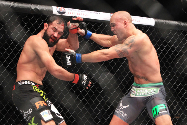 Robbie Lawler chases Johny Hendricks into the fence during their fight at UFC 181 Saturday, Dec. 6, 2014 at the Mandalay Bay Events Center. Lawlor won by split decision to claim the welterweight b ...