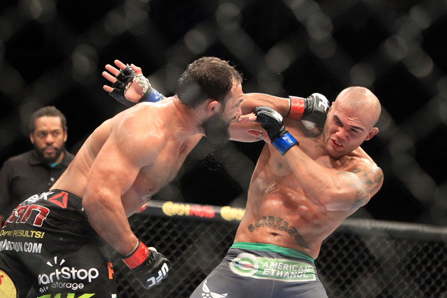 Robbie Lawler is hit by a left from Johny Hendricks during their fight at UFC 181 Saturday, Dec. 6, 2014 at the Mandalay Bay Events Center. Lawlor won by split decision to claim the welterweight b ...