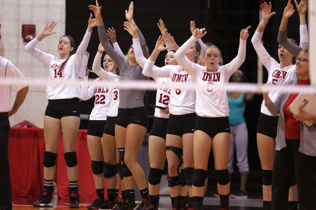 Members of the UNLV women's volleyball team celebrate winning a long rally in the second set against Fresno State at Cox Pavilion in Las Vegas Thursday, Sept. 25, 2014. UNLV went on to beat Fresno ...