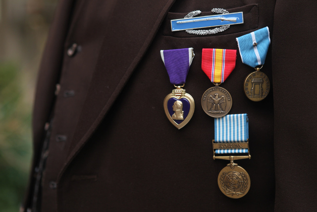 Korean War Army veteran Charles Mahoney poses for a photo in uniform with his service medals in front of his home in Las Vegas Thursday, Dec. 11, 2014.  Mahoney is currently waiting for compensati ...
