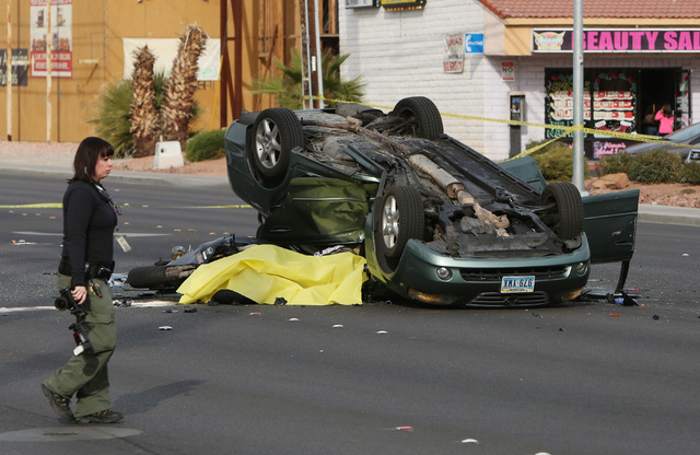 A Las Vegas police accident scene photographer is seen at the accident scene where two people died on the 3100 block of Valley View Blvd., on Saturday, Dec. 20, 2014.  (Bizuayehu Tesfaye/Las Vegas ...