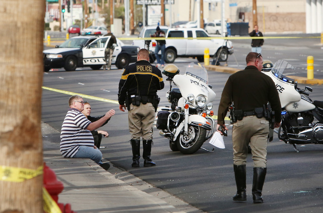 Unidentified people  talk to a Las Vegas police officer near the accident scene where two people died on the 3100 block of Valley View Blvd., on Saturday, Dec. 20, 2014.  (Bizuayehu Tesfaye/Las Ve ...
