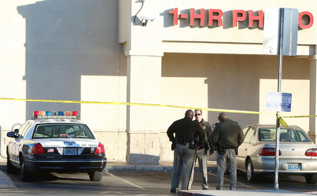 Las Vegas police officers stand outside a Walgreens where the robber shot and killed an employee in a back room at 8500 W. Cheyenne, near Durango on Friday, Dec. 26, 2014,  in Las Vegas police sai ...