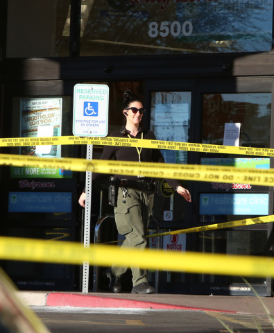 A Las Vegas police creime scene investigator is seen outside a Walgreens where the robber shot and killed an employee in a back room at 8500 W. Cheyenne, near Durango on Friday, Dec. 26, 2014,  in ...
