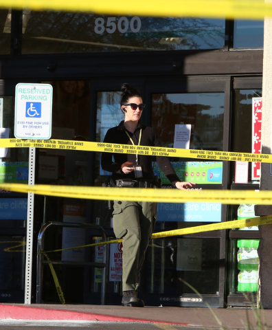 A Las Vegas police creime scene investigator exits a Walgreens where the robber shot and killed an employee in a back room at 8500 W. Cheyenne, near Durango on Friday, Dec. 26, 2014,  in Las Vegas ...