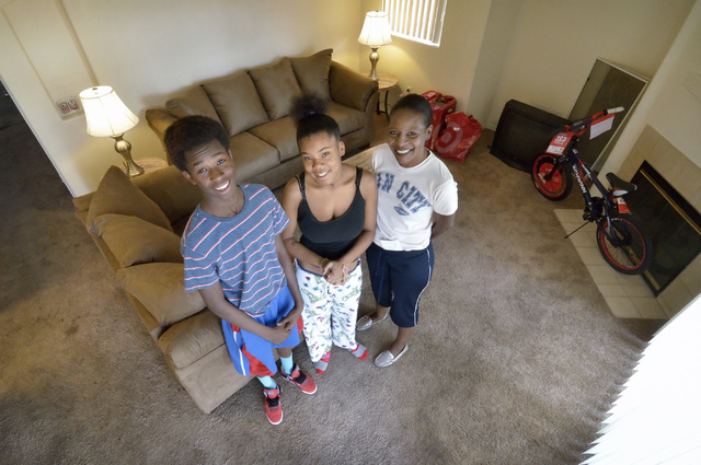 Theresa Carr, right, is shown with her grandchildren Ar'Zjon Carr, left, and Zakariyyaa McIntyre after a delivery of free furniture to her home near Craig Road and Nellis Boulevard on Saturday, De ...