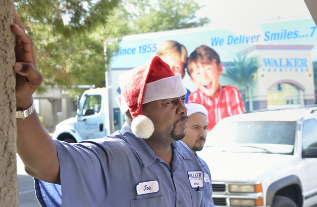 Joe Wayman, a delivery manager with Walker Furniture, left, and driver Luis Arellanes are shown after making a delivery of free furniture to the home of Theresa Carr near Craig Road and Nellis Bou ...