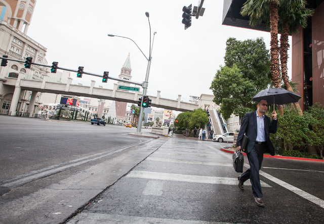 A man walks along the Strip holding an umbrella as it rains outside Treasure Island hotel-casino in Las Vegas on Tuesday, Dec. 2, 2014. (Chase Stevens/Las Vegas Review-Journal)