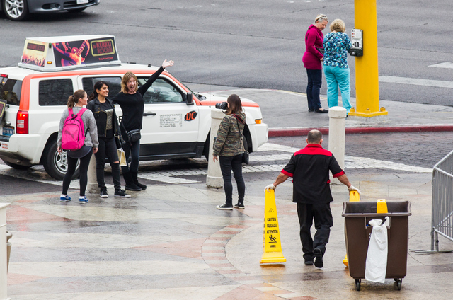 A janitor looks to put up warning signs as rain lightly falls outside of the Venetian hotel-casino in Las Vegas on Tuesday, Dec. 2, 2014. (Chase Stevens/Las Vegas Review-Journal)
