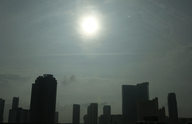 Buildings are silhouetted by the sun as it shines through the morning fog and clouds Friday, Dec. 5, 2014, in Las Vegas. Skies will clear slightly Friday afternoon, but another upper-level system  ...